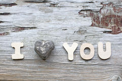I love you. Words I love you with stone heart on wooden vintage scratched background royalty free stock images
