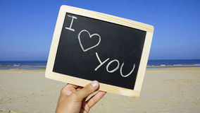I love you. Written on a chalkboard on the beach royalty free stock photo