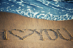 I love you - written in the sand. With a foamy wave underneath Stock Photo