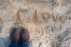 I love you written in the sand. Phrase i love you written in the sand next to man feet with old shoes stock image