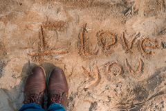 I love you written in the sand. Phrase i love you written in the sand next to man feet with old shoes stock photo