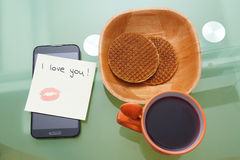 I love you written on a ticket with kiss with lipstick  on the s. Mart phone Royalty Free Stock Photography