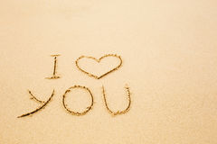 I love you written on wet yellow beach sand Royalty Free Stock Photos