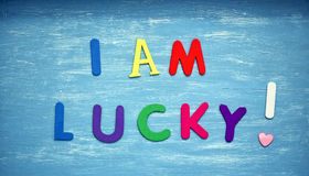I am lucky written on a blue wood background Stock Photo