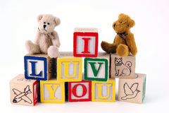 I Luv You with Bears. Bears sitting on toy blocks spelling 'I LUV YOU' on a white background Royalty Free Stock Photos