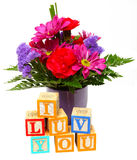 I Luv You with Flowers. Small vase of flowers behind blocks spelling I Luv You Stock Image