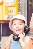 I'm calling Grandma. Little boy talking with grandma by pay phone Stock Images