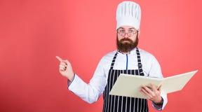 i m Conceito das artes culinárias O cozinheiro amador leu receitas do livro O homem aprende foto de stock royalty free