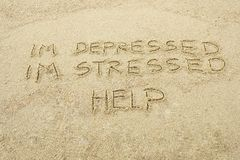 Depressed, stressed. HELP. I`m Depressed, I`m stressed and HELP written on sandn stock photography