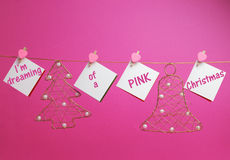 I'm dreaming of a PINK Christmas. Message written on hanging white signs with gold festive holiday ornaments against a pretty pink background Royalty Free Stock Image