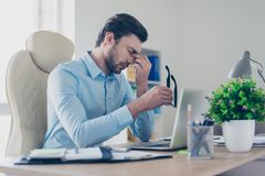 I`m exhausted, I can`t continue working! Tired sad depressed off. Ice worker clothed in stylish blue shirt, holding his black rimglasses and touching nose-bridge Stock Photography
