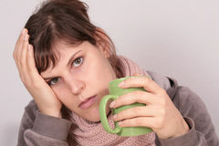 I'm Feeling Sick. This young woman drinks a cup of tea. her facial expression shows that she is feeling sick Stock Photos