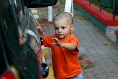 I'm getting the Door. Little Boy Unlocking the Car Door Royalty Free Stock Photos