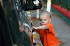 I'm getting the Door. Little Boy Unlocking the Car Door Royalty Free Stock Image