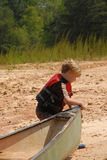I'm going canoeing. Young boy with life vest on getting a canoe ready to take for a spin Royalty Free Stock Photo