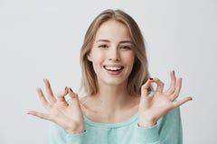 I ` m Handeln groß Frohe glückliche junge blonde Frau in der blauen Strickjacke breit lächelnd und okaygeste mit beiden Händen ma Stockfoto