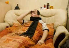 I`m ill series. White male in bed with high temperature having a headache Royalty Free Stock Images