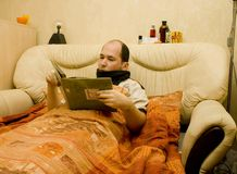 I`m ill series. White male in bed with high temperature readind a book Stock Photography