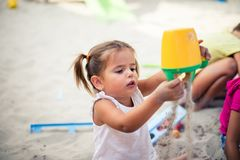 I`m a little creator. Toddler girl playing with sand. Close up. Space for copy royalty free stock image