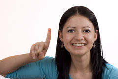 I'm Number One. Smiling young woman on white background holding up one finger Stock Images