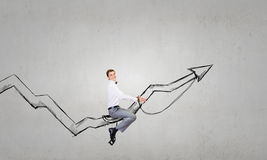 I'm reaching up to success!. Young businessman riding graph arrow going up Royalty Free Stock Image
