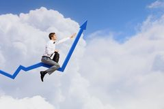 I'm reaching up to success!. Young businessman riding graph arrow going up Royalty Free Stock Photography