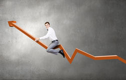 I'm reaching up to success!. Young businessman riding graph arrow going up Royalty Free Stock Photos