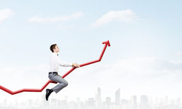 I'm reaching up to success!. Young businessman riding graph arrow going up Stock Images