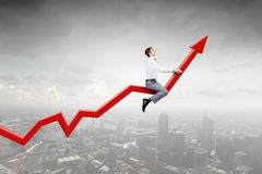 I'm reaching up to success!. Young businessman riding graph arrow going up Stock Photography