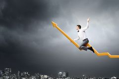 I'm reaching up to success!. Young businessman riding graph arrow going up Stock Photos