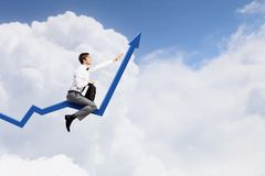 I'm reaching up to success!. Young businessman riding graph arrow going up Stock Photo