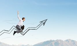 I'm reaching up to success!. Young businessman riding graph arrow going up Royalty Free Stock Images