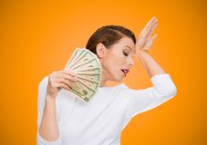 I'm rich spoiled drama queen. Portrait attractive woman model holding dollar banknotes lie fan, feels tired melancholic detached from reality, isolated orange Stock Photos