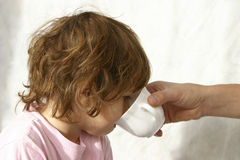When I'm sick. Father giving water in a white cup to his sick daughter Royalty Free Stock Image