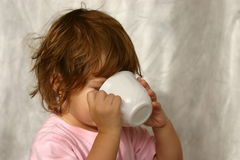 When I'm sick. Child drinking water from a white cup Royalty Free Stock Photos