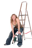 I'm a skillful worker!. A smiling woman with a drill sits on the stepladder Stock Photo