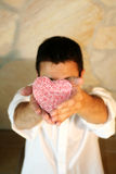 I´m sorry. Young man is holding a heart with roses in his hands Stock Images