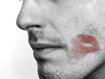I'm sorry... B&W photo of a mans face with a red lipstick kiss mark on the cheek royalty free stock photos