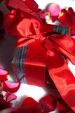 Valentine Gift. Gift box with red ribbon and rose petals Royalty Free Stock Photography