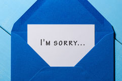 I`m SORRY - message in blue envelope. At wooden background stock photos