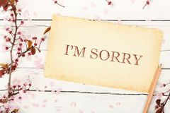 I`m sorry. On paper with almond tree twig on white wood Stock Photo