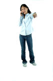 I'm Talking To You!. Young Asian girl talking on a cellphone pointing at you royalty free stock photography