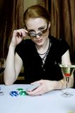 I'm unbeatable. Attractive red-haired woman poses victoriously with a confident expression, after winning a poker game Royalty Free Stock Photo