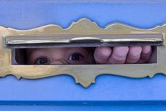 I´m watching you. A child looks through an slit Royalty Free Stock Image