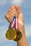 I'm winner!. Hand hold gold medal in blue sky background Stock Photos