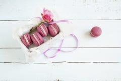 I maccheroni francesi cremisi dolci e sono aumentato con la scatola su fondo di legno tinto luce immagini stock