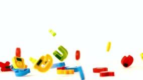 I magneti dell'alfabeto che cadono sul bianco sorgono video d archivio