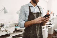 I manage all process online. Close up portrait of young male jeweler in apron holding a smartphone. While standing at his jewelry workshop royalty free stock photography