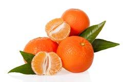 I mandarini arancio, le clementine, i mandarini o le piccole arance con uno si sono sbucciati e taglio a metà con le foglie Fotografia Stock Libera da Diritti