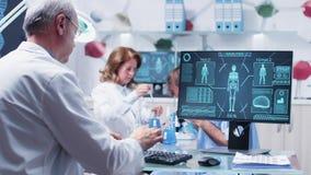 I manliga forskaretyper för upptaget laboratorium på datortangentbordet stock video
